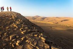 People standing desert mountain peak, south Israel arid landscape royalty free stock images