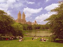 Many people rest on the grass lawn of Central park, skyscrapers peeks out of the trees on background stock photo