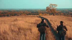 People tourists travel in nature the autumn adventure. slow motion video. two hiker outdoor with backpacks hiking stock footage