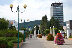 People in town centre enjoy nice day, high Administrative building of state agencies in background Stock Photos