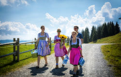 People in traditional austrian costumes. SCHEFFAU, TIROL, AUSTRIA - AUGUST 28, 2016. People in traditional austrian costumes on the road on the mountains in Stock Image