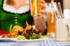 People in traditional Bavarian Tracht eating in restaurant or pub. Young people in traditional Bavarian Tracht eating in restaurant or pub lunch or dinner, focus Stock Photography