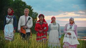 People in traditional folk clothes walking on the field and singing a song - sunset. Mid shot stock video footage