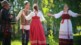People in traditional Russian clothes are dancing on the field holding hands - one of them plays the accordion music. Mid shot stock footage