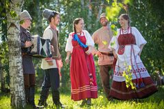 People in traditional Russian clothes are dancing in the field and talking - one of them plays the accordion music. Gorizontal view stock image