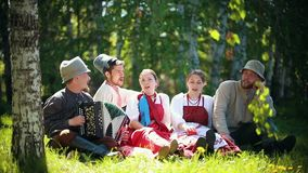 People in traditional Russian clothes sit on the lawn and singing by the accordion. Mid shot stock video footage