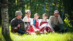 People in traditional Russian clothes sit on the lawn and talk. Mid shot stock video footage
