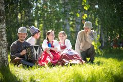 People in traditional Russian clothes sit on the lawn and talk - one of them plays the accordion and smile. Gorizontal view stock photo
