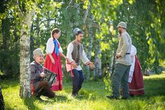 People in traditional Russian clothes are talking on the field and have fun - one of them plays the accordion and. Singing - gorizontal view stock photo