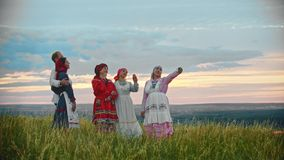 People in traditional russian folk clothes standing on the field and taking a selfie. Mid shot stock video