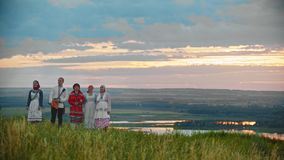 People in traditional russian folk clothes walking on the field. Mid shot stock video footage