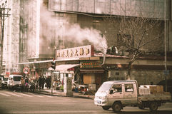 People and traffic around commercial building around Dalian trai Royalty Free Stock Photos