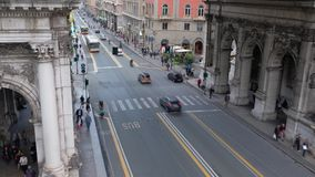 People and traffic passing by in the main street of Genoa, Via XX Settembre stock footage
