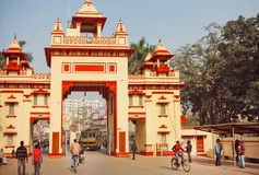 People traffic and rushing students walking past the gates of the University. VARANASI, INDIA - JANUARY 3: People traffic and rushing students walking past the royalty free stock image