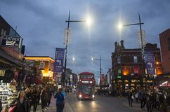 People and traffic on street at dusk in Camden Town London Royalty Free Stock Image