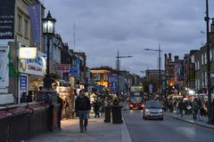 People and traffic on street at dusk in Camden Town London Stock Photo