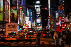 People and Traffic in Times Square New York City. Buses and taxis wait in traffic under the colorful billboards and bright lights of the Times Square area in mid stock images