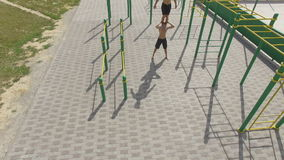 People train on an outdoor sports field in summer, aerial shot stock video