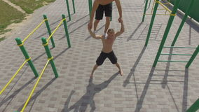 People train on an outdoor sports field in summer, aerial shot stock footage