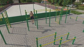 People train on an outdoor sports field in summer, aerial shot stock video footage