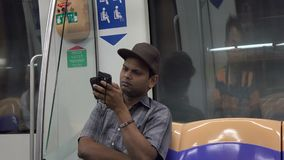 People on the train station in Singapore. A man sitting on the Mass Rapid Transit train in Singapore. The MRT network encompasses 170.7 kilometres (106.1 mi) of stock video footage