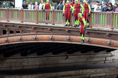 People trained in diving suits, jump into the water from the bridge Royalty Free Stock Photos