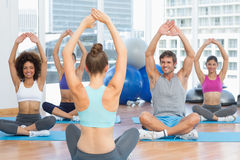 People with trainer doing stretching exercises in gym Royalty Free Stock Photography