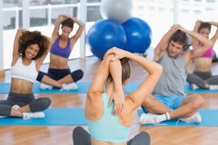 People with trainer stretching hands behind backs. Young people with trainer stretching hands behind backs in a bright gym royalty free stock photos