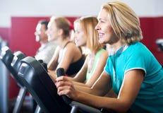 People training on exercise bikes together Stock Photo
