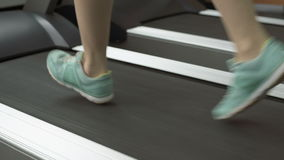 People training in fitness club, gym and sport activity. Woman exercising and running on treadmill. Pretty girl running in the simulator, jogging track stock video footage