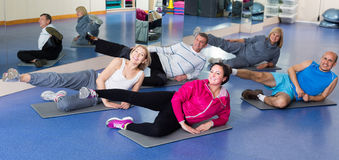 People training in a gym on sport mats. Elderly happy people training in a gym on sport mats Stock Images