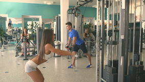 People training in the gym. Sports people performs strength exercises. Couple pulling the blocks in the simulator. The girl with the man practicing on the stock video