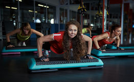 People training in the gym. Strong girls doing push ups exercise on step boards in fitness class. Sport, power and recreation concept Stock Photo