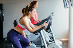 People traning in gym on various machines Stock Photo