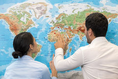 People in Travel Agency Office Concept. Young men and women standing near map in travel agency office Royalty Free Stock Image