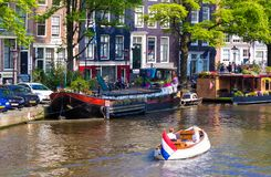 People travel by boat along the canals of Amsterdam at summer time. Royalty Free Stock Photography