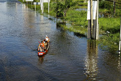 People travel by boat on the road during flood Stock Photos