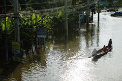 People travel by boat on the road during flood. PATHUMTHANI, THAILAND - OCTOBER 16 : Unidentified people have to travel by boat on the road during flooding Royalty Free Stock Image