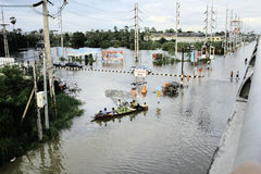 People travel by boat on the road during flood. PATHUMTHANI, THAILAND - OCTOBER 16 : Unidentified people have to travel by boat on the road during flooding Royalty Free Stock Images