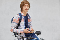 People, travel, technology, leisure and lifestyle concept. Young male standing near his bike holding modern smart phone in hands l royalty free stock photography
