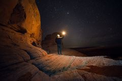 People Travel to scenic destination concept. Tourist man walking holding the light traveling in mountains and enjoy the night sky. View full of start at night royalty free stock photos