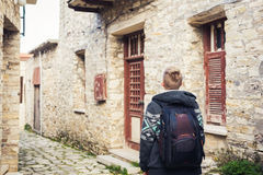 People, travel and tourism - man with backpack walking along old town street Stock Images
