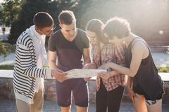 Friends travelers searching the location on map. People travel, vacation, holidays, friendship, city tour. Friends travelers searching the location on map Royalty Free Stock Photography