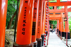 People travel and walking path inside through a tunnel of torii Stock Image