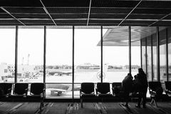 People traveling on airport; waiting at the plane boarding gates. Stock Photos