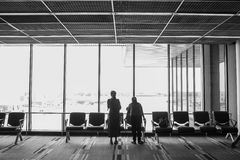 People traveling on airport; waiting at the plane boarding gates. Stock Photo