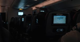 People traveling by blane at night. Dark cabin with working seat monitors. Inside view of plane cabin at night. Rows of seats with passengers and displays stock footage