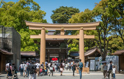 People are traveling in to Meiji Shrine through the wooden gate. Stock Photo