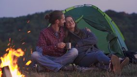 People Traveling To Nature, Couple Near Camp. People Traveling To Nature, Couple Sitting Near Camp Drinking Hot Drinks And Enjoying Travel On Weekend stock video footage