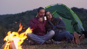 People Traveling To Nature, Couple Near Camp. People Traveling To Nature, Couple Sitting Near Camp Drinking Hot Drinks And Enjoying Travel On Weekend stock footage